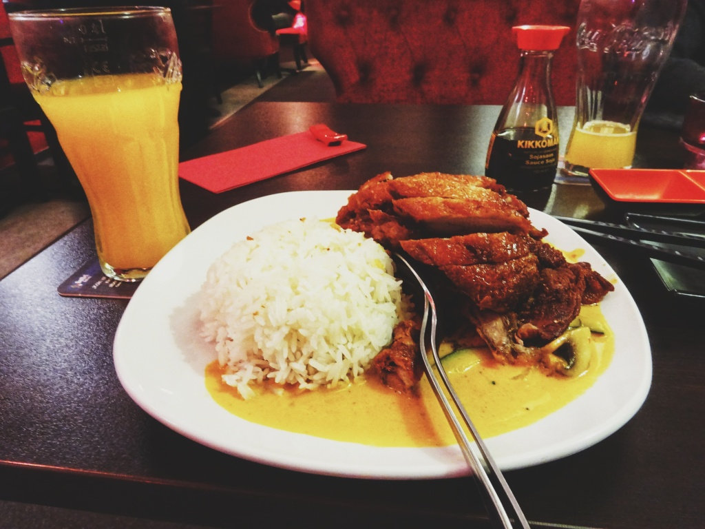A glass of Mango Juice with a plate of rice, duck and a yellow sauce