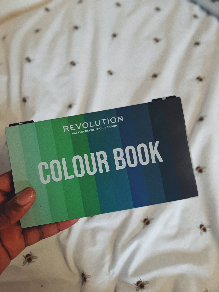 Chizoba is holding the Makeup Revolution's Colour Book Shadow Palette CB05.