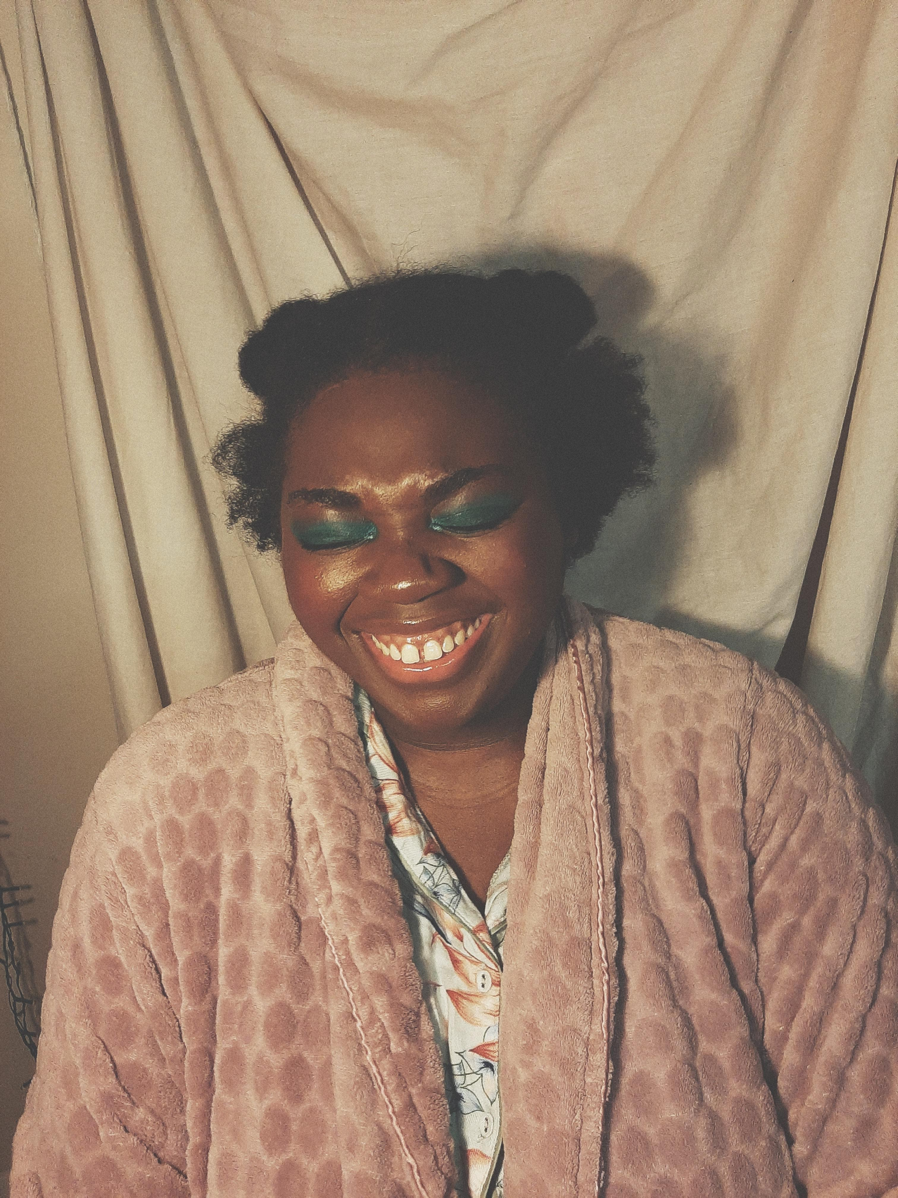 Chizoba is smiling with her eyes closed. she is wearing a full face of make-up including green eyeshadow and clear lipgloss. she is also wearing green floral pyjamas and a pink dressing gown