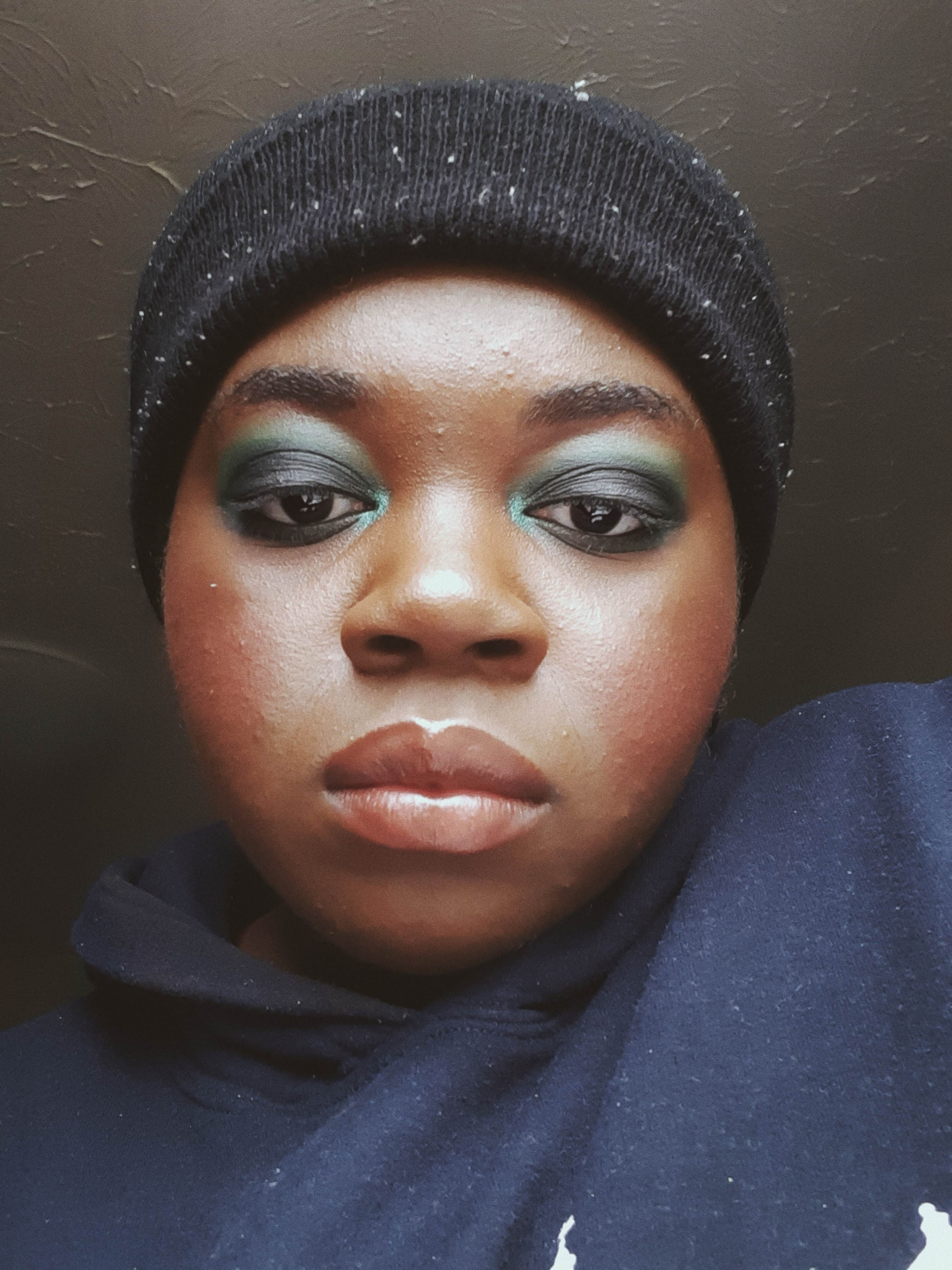 Chizoba is wearing a black beanie and a navy hoodie. she is wearing a full face of makeup including dark green smokey eyeshadow and nude lip gloss. she is giving a smouldering expression