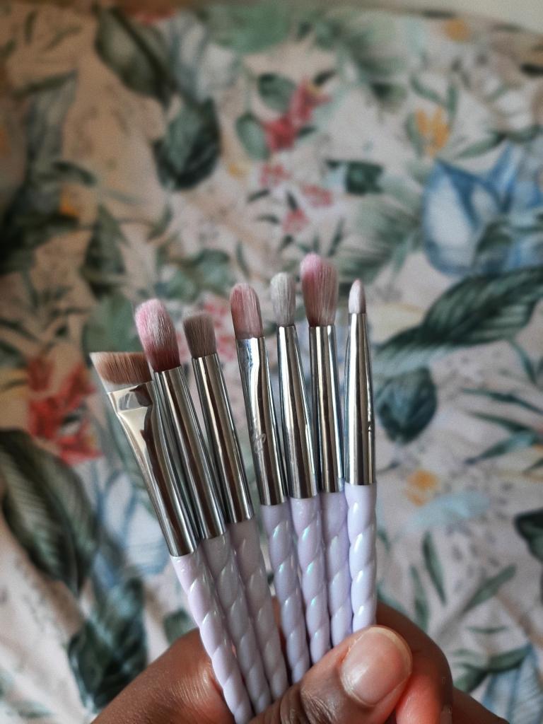 Chizoba is holding the Unicorn Cosmetics Class of 86' Makeup Brush Set
