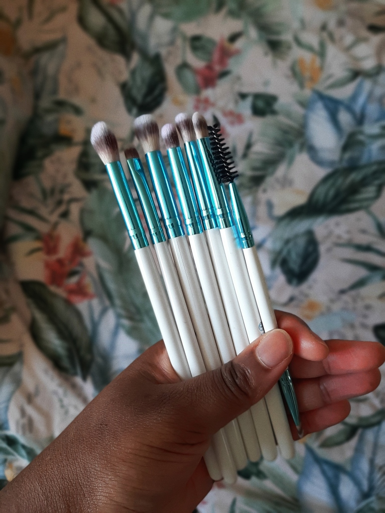 Chizoba is holding the smaller brushes of the BH Cosmetics Poolside Chic Brush Set