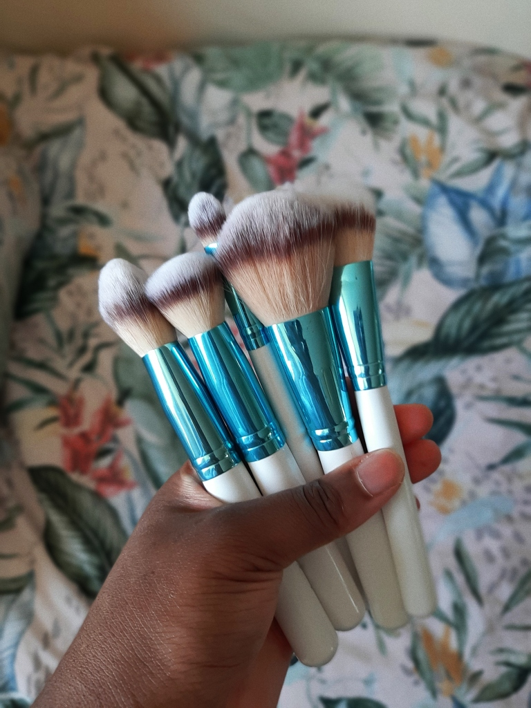 Chizoba is holding the bigger brushes of the BH Cosmetics Poolside Chic Brush Set
